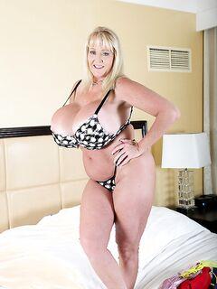 Веселая баба с огромными сиськами в спальне на постели - секс порно фото