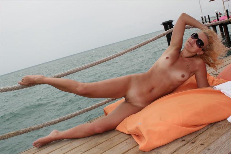 Сексапильная женщина ходит по саду и отдыхает на берегу моря - секс порно фото