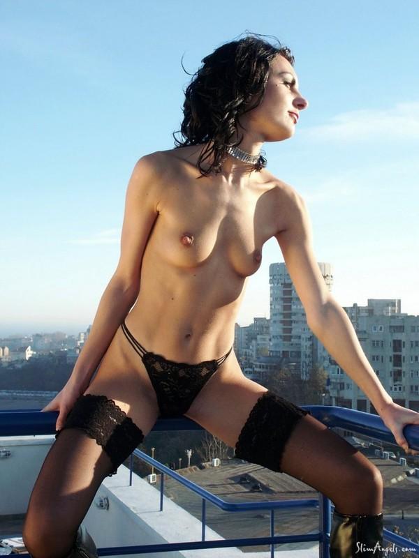 Сексапильная брюнетка в чулках и сапогах на крыше дома - секс порно фото