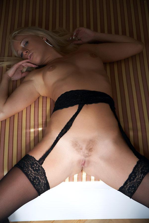 Худенькая блондинка красиво позирует на камеру в чулках - секс порно фото