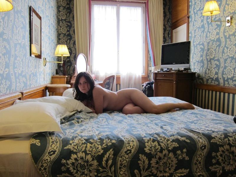Очаровательная брюнетка валяется на кроватке нагишом - секс порно фото