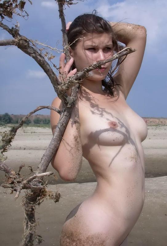 Голая брюнетка позирует на жарком песочке - секс порно фото