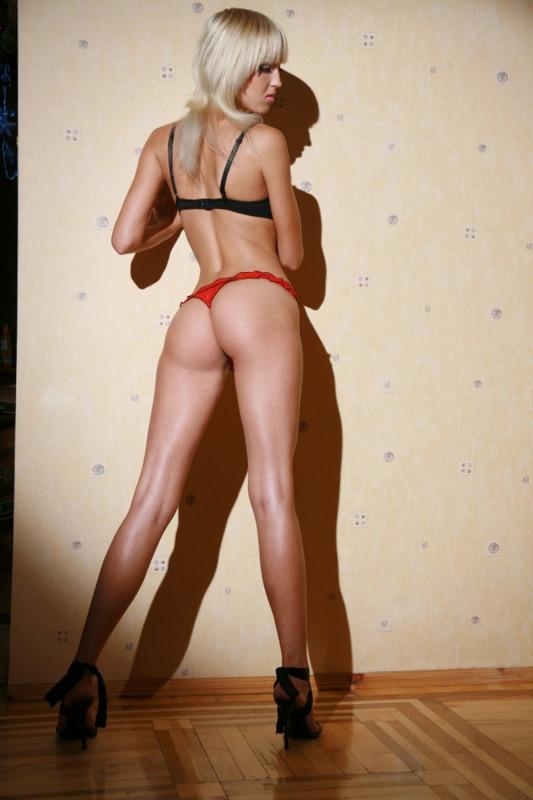 Стройная блондинка красиво позирует возле стены - секс порно фото