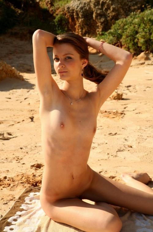Тощая молодая девушка позирует на песочном пляже - секс порно фото