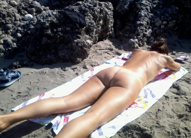 Обнаженная девушка загорает на берегу моря - секс порно фото